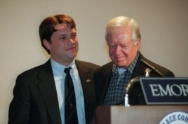 FILE - Former President Jimmy Carter, right, smiles after being introduced by grandson Jason Carter during a symposium on South Africa sponsored by the Peace Corps at Emory University in Atlanta.