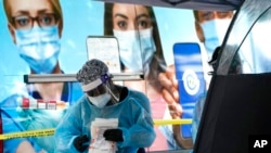 Seorang tenaga kesehatan memeriksa peralatannya saat bertugas di lokasi tes COVID-19, di Miami, AS, Rabu, 18 November 2020. (Foto: dok).