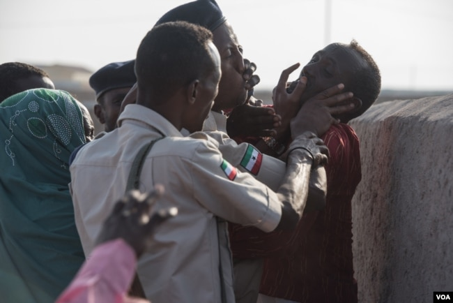 Police clash with families who don't want a mass grave containing their relatives to be exhumed in Berbera, Somaliland. (J. Patinkin/VOA)