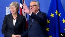 El presidente de la Comisión Europea, Jean-Claude Juncker (D), saluda a la primera ministra británica Theresa May en la sede de la UE en Bruselas, el miércoles 21 de noviembre de 2018.