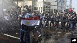 示威者面对高压水龙,手持国旗