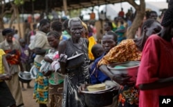 FILE - South Sudanese refugees queue to receive a lunch of maize mash and beans, at the Imvepi intake center, where newly-arrived refugees are processed before being transferred to the nearby Bidi Bidi refugee settlement, in northern Uganda, June 6, 2017.