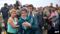 A migrant cries as she tries to break through the cordon of Macedonian police forces, while waiting to board a bus after crossing the Macedonian-Greek border near Gevgelija on Sept. 10, 2015.