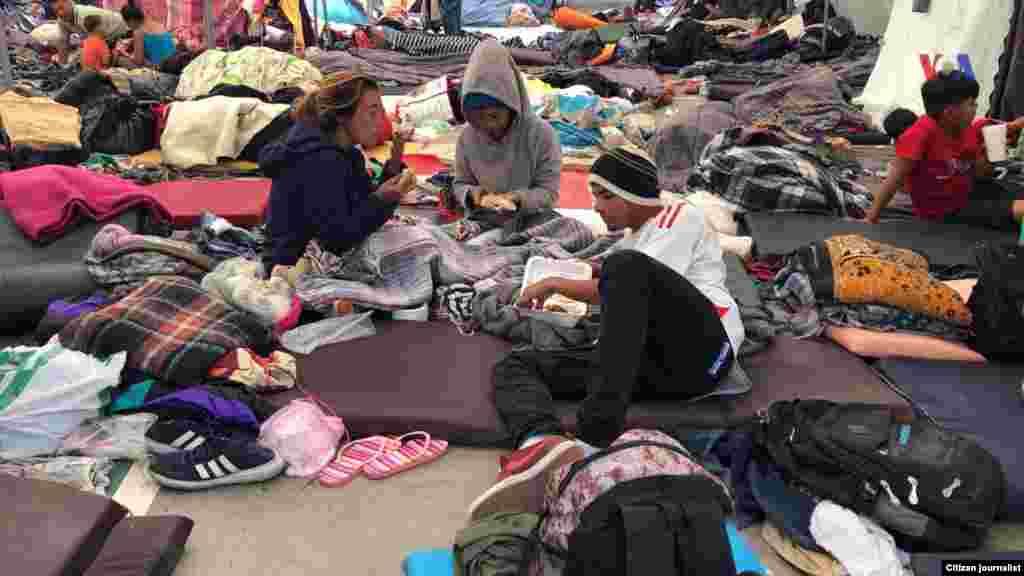 Los migrantes de Centro América se encuentran en un alburgue en Tijuana. En esta imagen se aprecia personas compartiendo alimentos en el piso. Fotografía: Celia Mendoza- VOA