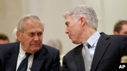 FILE - Supreme Court Justice Neil Gorsuch, right, talks with former Defense Secretary Donald Rumsfeld, right, at the 50th anniversary of the Fund for America Studies luncheon at the Trump Hotel in Washington, Thursday, Sept. 28, 2017.