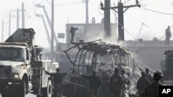 The debris of a bus attacked by Taliban fighters during a gunbattle, is removed from the site on the outskirts of Kabul, Afghanistan, 19 Dec 2010