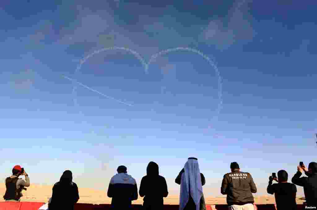 People watch as aircrafts perform during an airshow at Saudi Aviation Forum at Thumamah airport, in Riyadh, Saudi Arabia.