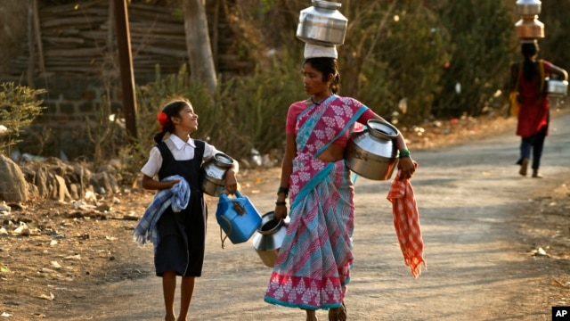 In this Wednesday, March 13, 2013 photo, Indian villagers walk to fetch drinking water at Kasu village, in the western Indian state of Maharashtra.