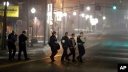 지난 12일, 퍼거슨 지역 경찰관들이 동료 두 명이 총격당한 현장을 조사하고 있다.