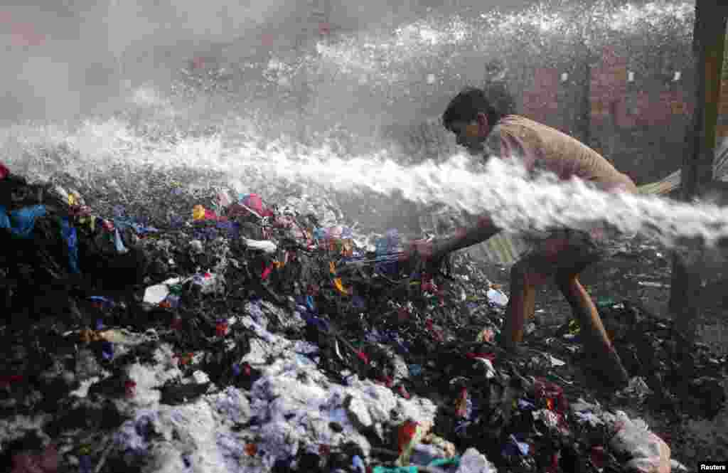 방글라데시 다카시의 면공장 물류창고에 화재가 발생한 가운데, 한 남성이 화재 더미에서 물건을 꺼내려 하고 있다.