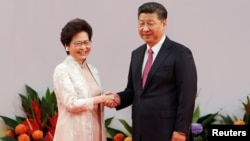 FILE - Hong Kong Chief Executive Carrie Lam shakes hands with Chinese President Xi Jinping after she swore an oath of office on the 20th anniversary of the city's handover from British to Chinese rule, in Hong Kong, China, July 1, 2017.