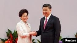 Pemimpin Hong Kong Carrie Lam berjabat tangan dengan Presiden China Xi Jinping setelah dia mengucapkan sumpah jabatan pada peringatan 20 tahun penyerahan kota tersebut dari pemerintah Inggris kepada China, di Hong Kong, China, 1 Juli 2017. (REUTERS/Bobby Yip).