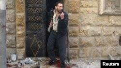 Čovek stoji ispred zgrade u pobunjeničkom delu Alepa, koja je pogođena u vazdušnim napadima