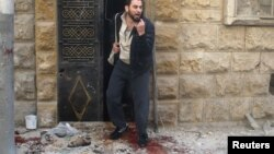 A man reacts as he stands on bloodstains at a site hit by airstrikes in the rebel-held area of Aleppo's al-Fardous district, Syria, April 29, 2016.