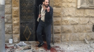 A man reacts as he stands on blood stains at a site hit by airstrikes in the rebel held area of Aleppo's al-Fardous district, Syria, April 29, 2016.