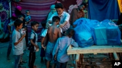 A Rohingya activist distributes new clothes among refugees at a refugee camp alongside the banks of the Yamuna River in the southeastern borders of New Delhi, sprawling Indian capital, July 1, 2021. (AP Photo/Altaf Qadri)