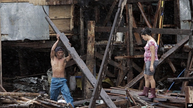 A man salvages a wood to repair his shanty destroyed during the height of typhoon Nesat as rains pour due to Typhoon Nalgae in Navotas town, north of Manila, Philippines, October 1, 2011.