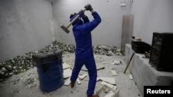 A customer wearing protective gear smashes old furniture with a hammer in an anger room in Beijing, China January 12, 2019. Picture taken January 12, 2019.