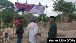 Sejumlah warga yang berada di lahan lokasi pemukiman baru yang akan didirikan 36 unit hunian tetap berupa rumah panggung Risha untuk 36 keluarga nelayan yang kehilangan rumah akibat terjangan tsunami teluk Palu. (Foto: VOA/Yoanes Litha)