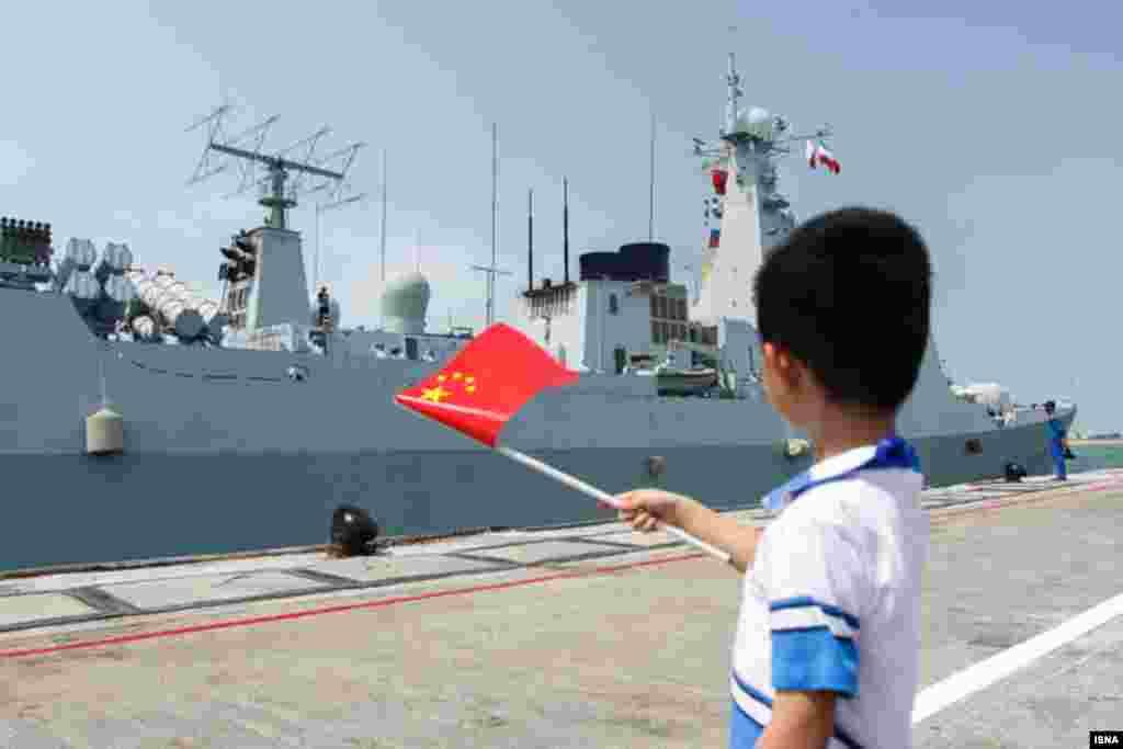 کودکانی در بندرعباس ردیف شدند تا برای پهلو گرفتن ناو نیروی دریایی چین، پرچم تکان دهند. عکس: امیرحسین خورگویی
