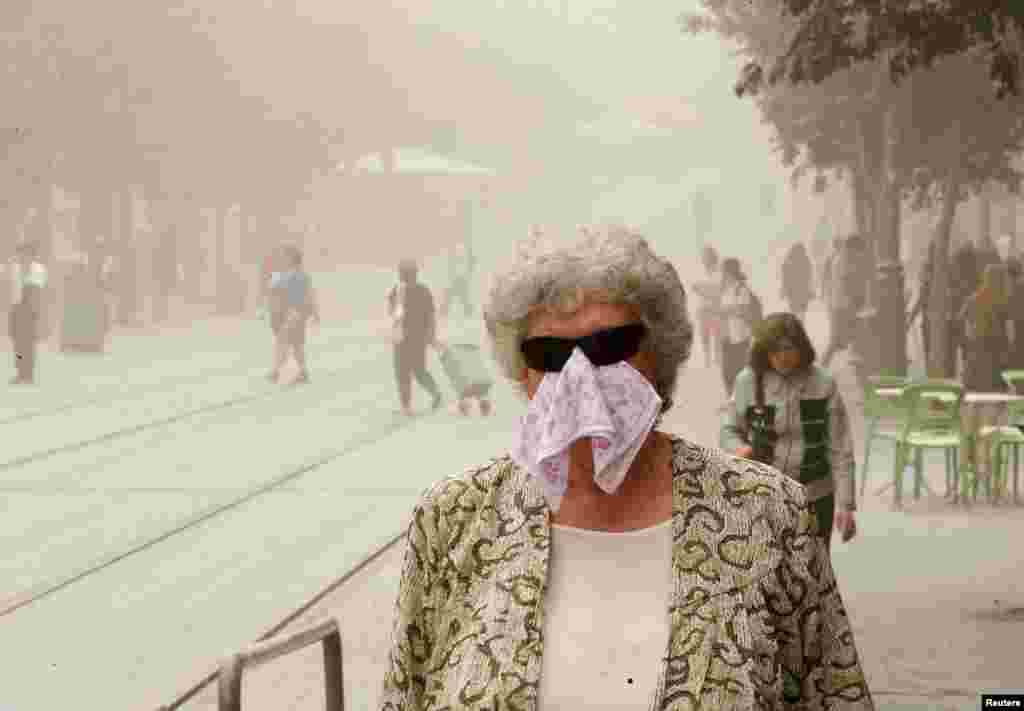 A pedestrian walks with a covered face during a sandstorm in Jerusalem. A heavy sandstorm swept across parts of the Middle East, killing two people and hospitalising hundreds in Lebanon and disrupting fighting and air strikes in neighboring Syria.