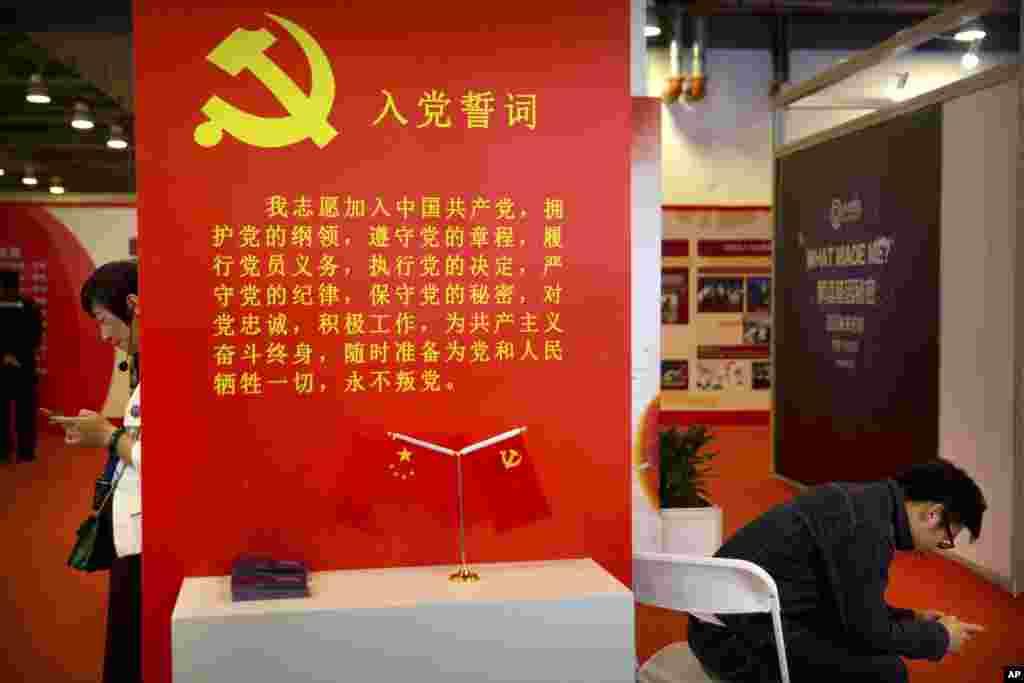 """2018年9月26日,在北京的中国改革开放40周年展览会上,参观者使用智能手机。展品中有中共入党誓词。中共9000万党员中,有多少人真正相信和实践""""为共产主义奋斗终生,随时准备为党和人民牺牲一切""""这些誓词?很多人认为,中国真心相信共产主义者很少很少。"""