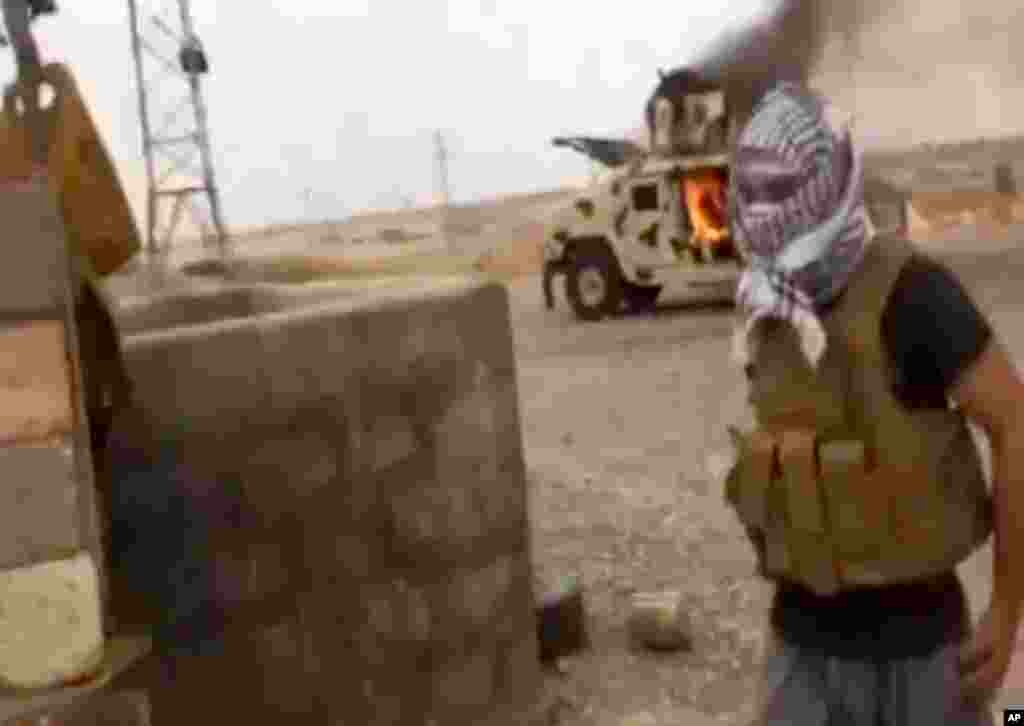 This image from video posted by Iraqi0Revolution, a group supporting ISIL, shows a militant standing in front of a burning Iraqi Army Humvee in Tikrit, Iraq, June 11, 2014.