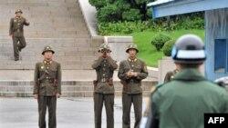 Северокорейские пограничники наблюдают за южнокорейскими солдатами на границе между двумя Кореями в демилитаризованной зоне у деревни Панмуньджон. 15 июля 2011 года