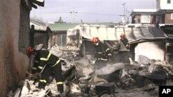 韩国消防队员在检查被北韩炮弹炸毁的房屋