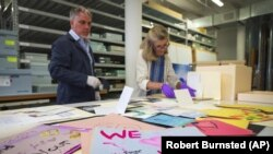 Jan Ramirez, chief curator at the 9/11 Memorial & Museum, right, sifts through a collection of condolence cards for a victim of 9/11 that were donated to the museum's archive, July 16, 2021, in Jersey City, New Jersey. (AP Photo/Robert Bumsted)