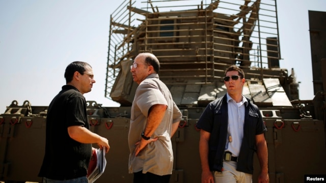 Israeli Defense Minister Moshe Yaalon (C) stands in front of an armored personnel carrier (APC) during a visit to a military base near Kibbutz Kissufim outside the central Gaza Strip, May 7, 2013.
