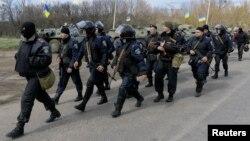 Các thành viên Bộ Nội vụ Ukraina đi qua xe bọc thép tại một chốt kiểm soát gần thị trấn Izium, miền đông Ukraine, ngày 15/4/2014. Tổng thống lâm thời Ukraine Oleksander Turchynov cho biết quân đội Ukraine đã chiếm lại phi trường Kramatorsk từ các phần tử chủ chiến ly khai thân Nga.