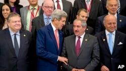 El secretario de Estado, John Kerry, conversa con el canciller jordano, Nasser Juden, mientras preparan la pose para la foto de la Conferencia de Donantes para Gaza.