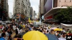 Algunos manifestantes portaban paraguas amarillos, que simbolizan el movimiento pro democracia Occupy Central, durante marcha de protesta en el día del décimo noveno aniversario de la entrega de Hong Kong por parte del Reino Unido a China.