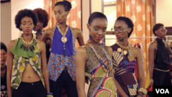 Models wearing East African designer wear prepare for a runway show in Kampala. May 17, 2014. (Hilary Heuler / VOA News)