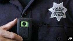 Un oficial de la policía de Oakland muestra una cámara de video portatil que puede grabar los procedimientos en los que participa.