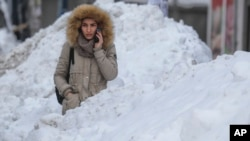 FILE - A woman waits between large piles of snow at a bus stop in Bucharest, Romania, Jan. 11, 2017. A study in Romania says snow has a freshness date, of sorts, for consumption.