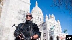 """Seorang polisi Perancis mengamankan basilika """"Sacre Coeur"""" di Paris, Minggu (15/11). Kelompok ISIS mengancam akan menjadikan Washington DC target serangan seperti Paris."""