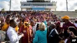 Democratic presidential candidate Hillary Clinton waves while visiting a homecoming game for Bethune-Cookman University Wildcats in Daytona Beach, Fla., Oct. 29, 2016, on her way to a rally.