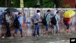 ພວກຜູ້ຊາຍ ຫຼາຍຄົນກຳລັງ ຍ່າງຜ່ານ້ຳຖ້ວມທາງ ໃນຂະນະ ທີ່ຝົນກຳລັງ ຕົກລົງຢ່າງຕໍ່ເນື່ອງ ຢູ່ເມືອງ Jammu ປະເທດ India, ວັນທີ 16 ສິງຫາ 2014.