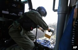 This U.S. Coast Guard image shows Petty Officer 2nd Class Kenneth Krowel dropping a box of MRE's to stranded residents near Utuado, Puerto Rico, Oct. 3, 2017. Nearly two weeks after the storm, 95 percent of electricity customers remain without power.