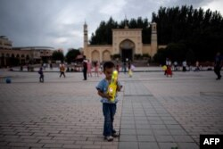 Seorang anak memegang mainan di depan Masjid Id Kah di Kashgar di Daerah Otonomi Xinjiang Uighur China, sehari sebelum liburan Idulfitri, 25 Juni 2017. (Foto: AFP)