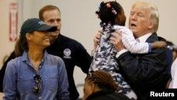 """Президент США Дональд Трамп піднімає маленьку дівчинку під час візиту з першою леді Меланією Трамп до центру допомоги постраждалим від урагану """"Гарві"""" в Г'юстоні, штат Техас, 2 вересня 2017 року."""