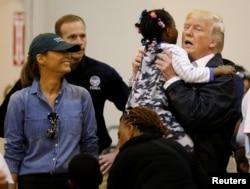 """Президент США Дональд Трамп піднімає маленьку дівчинку під час візиту з першою леді Меланією Трамп до Г'юстона і зустрічі з постраждалими від урагану """"Гарві"""". 2 вересня 2017 року."""