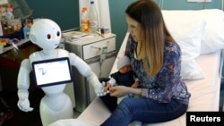 "FILE - New recruit ""Pepper"" the robot, a humanoid robot designed to welcome and take care of visitors and patients, holds the hand of a new born baby next to his mother at AZ Damiaan hospital in Ostend, Belgium June 16, 2016. (REUTERS/Francois Lenoir)"
