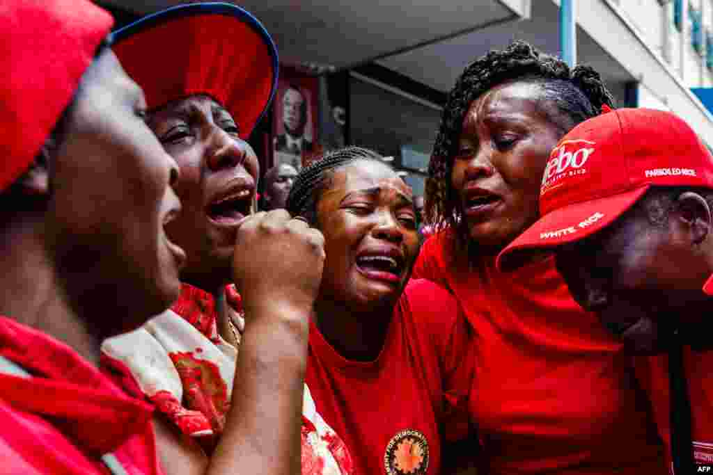 Supporters of the Zimbabwe opposition party Movement for Democratic Change (MDC) cry outside Harvest House, the party headquarters, in Harare following the death of the veteran leader Morgan Tsvangirai. Tsvangirai died of cancer at the age of 65.
