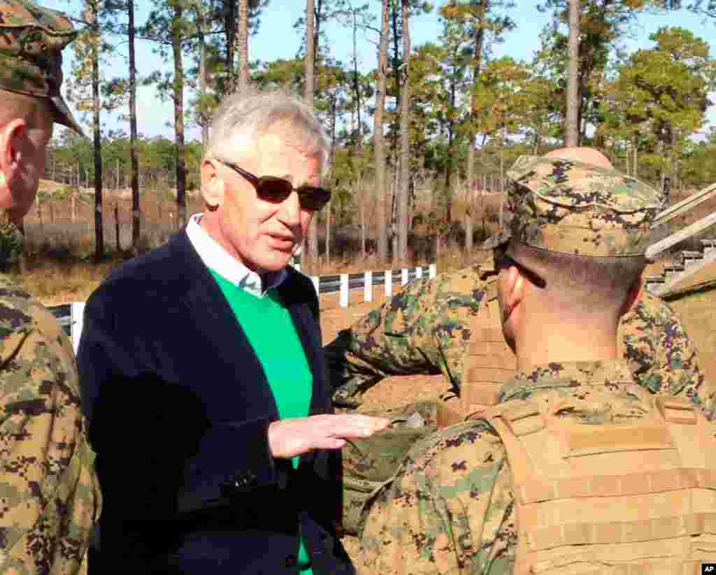 Defense Secretary Chuck Hagel talks to marines at a training range as he observes an experimental infantry unit that is going to help assess which combat jobs can be opened to women in 2016, Camp Lejeune, North Carolina, Nov. 18, 2014.