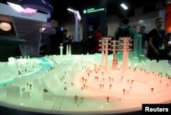 FILE - A portion of a city model glows red, indicating a cyberthreat to infrastructure, at the DarkMatter booth during the Black Hat information security conference in Las Vegas, July 26, 2017.