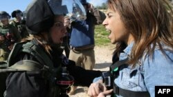 FILE - Palestinian activist Lema Nazeeh argues with an Israeli soldier following a protest march against Israeli settlements, near the West Bank village of Bilin, Jan. 30, 2015.