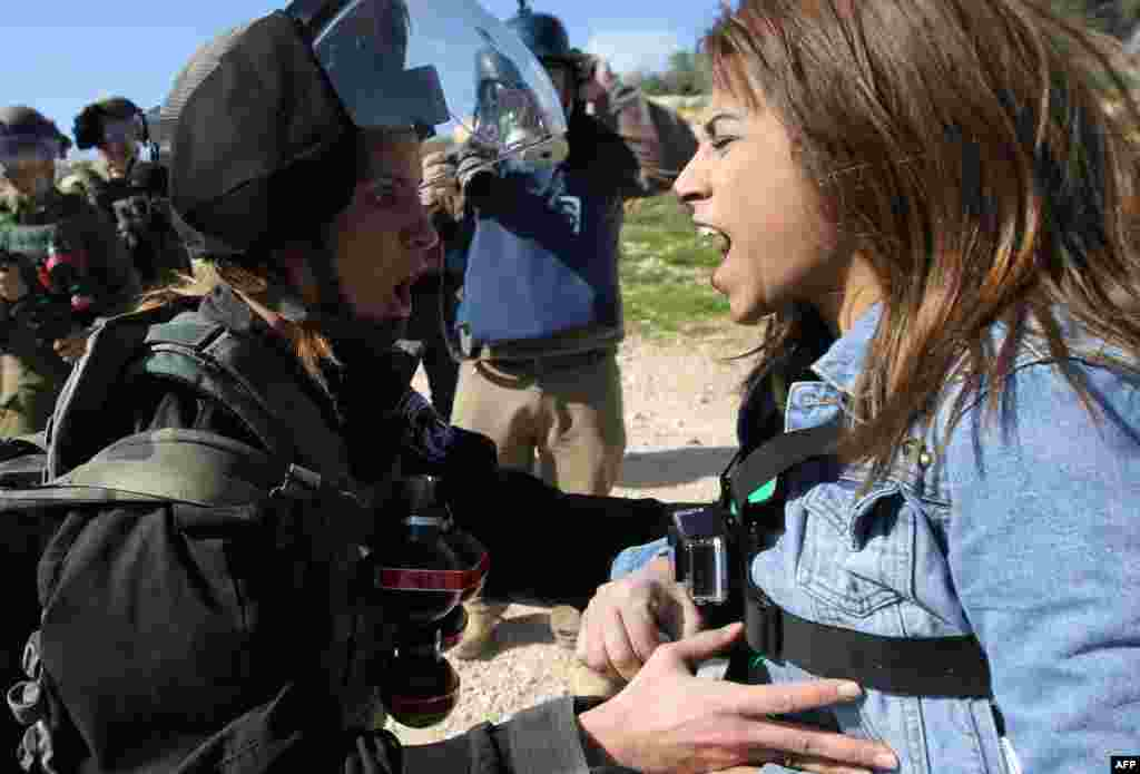 Palestinian activist Lema Nazeeh argues with an Israeli soldier during clashes between security forces and Palestinians from the West Bank village of Bilin, following a march to protest against Israeli settlements, in Bilin, west of Ramallah.